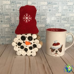 snowman made with wine corks sitting next to a coffee mug